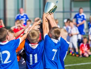 Young Soccer Players Holding Trophy. Boys Celebrating Soccer Foo